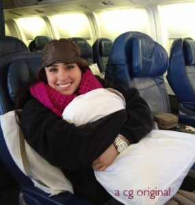 Chelsey with an eye mask and pillow waking up on a  flight from Paris to Chicago.