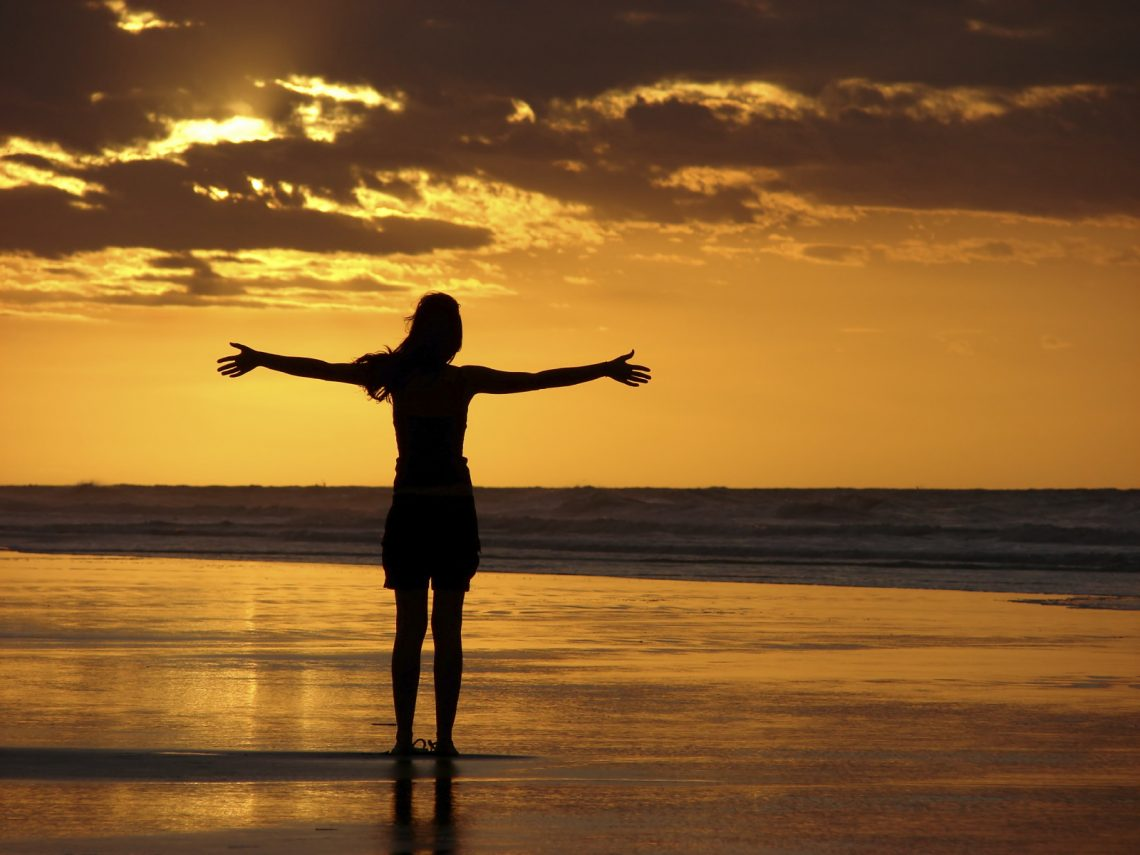 Woman on a beach surrendering arms wide open to the sunset.