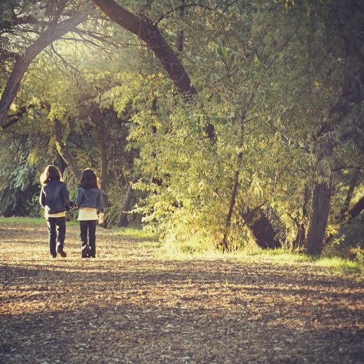 Two girls holding hands walking through the woods