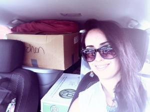 Picture of Chelsey in her car loaded with boxes
