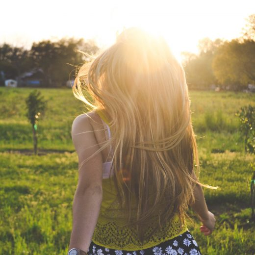 View of the back of a girl running in a field as the sun is setting in front of her.