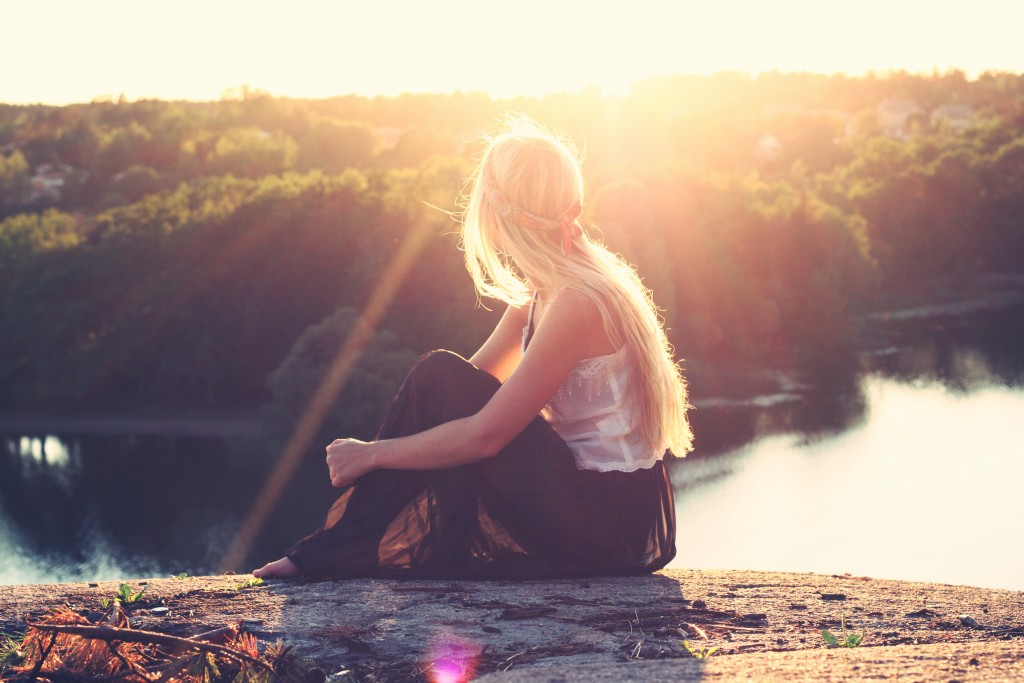Girl sitting at an overlook as the sun sets.